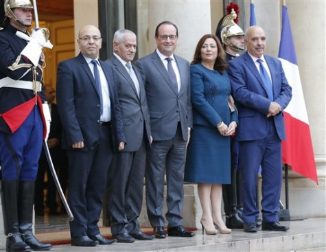 France President Francois Hollande, center, welcomes the four Nobel Peace Prize winners Mohamed Fadhel Mafoudh head of the Tunisian Bar Association, left, Houcine Abassi secretary general of the Tunisian General Labour Union, 2nd left, Wided Bouchamaoui president of the Tunisian employers, 2nd right, and Abdessattar Ben Moussa president of the Tunisian Human Rights League, right, at the Elysee Palace in Paris, France, Friday, Oct. 16, 2015. The 2015 Nobel Peace Prize went to the Tunisian National Dialogue Quartet who steered Tunisia away from civil war and toward democracy after its 2011 revolution. (AP Photo/Michel Euler)