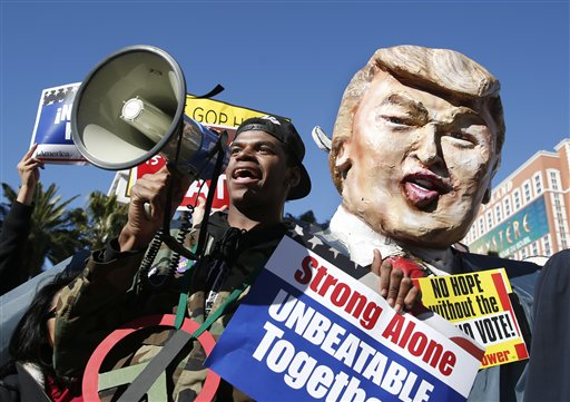 Protestors carrying a likeness of Republican presidential candidate Donald Trump gather outside the Venetian Hotel & Casino before the CNN Republican presidential debate on Tuesday, Dec. 15, 2015, in Las Vegas. (AP Photo/John Locher)