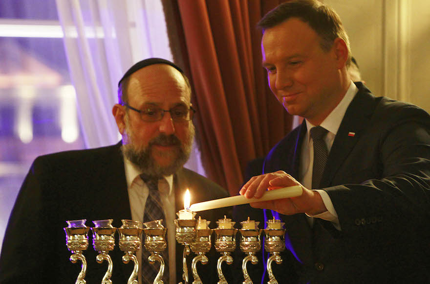 Poland's President Andrzej Duda lights a Hanukkah candle alongside Poland's Chief Rabbi Michael Schudrich in Warsaw, Poland, on Wednesday Dec. 9, 2015. In marking the Jewish festival of lights, Duda follows an example set by earlier Polish presidents in the post-communist era. Poland was once home to the world's largest Jewish population; most of the country's Jews were killed by Germany during the Holocaust. (AP Photo/Czarek Sokolowski)