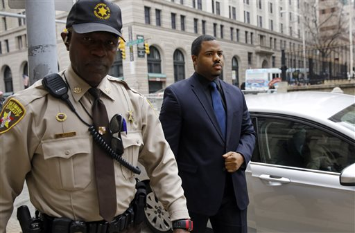 Officer William Porter, right, one of six Baltimore city police officers charged in connection to the death of Freddie Gray, walks into a courthouse during jury deliberations, Wednesday, Dec. 16, 2015, in Baltimore. Jurors are in their third day of deliberations in the manslaughter trial of Officer William Porter. (AP Photo/Patrick Semansky)