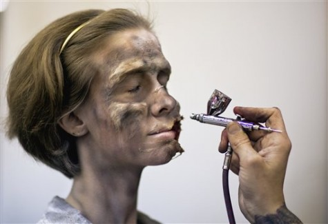 "Lacy Dearring, of Lawrenceville, Ga., left, is worked on by makeup artist Lucas Godfrey to look like a zombie at Walker Stalker Con, a convention based off the cable TV show ""The Walking Dead,"" Sunday, Nov. 3, 2013, in Atlanta. The convention, which ran through the weekend, was expected to draw about 10,000 participants says co-creator Eric Nordhoff. ""The Walking Dead"" characters battle zombies known as ""walkers"" in the streets of downtown Atlanta and in forests, small towns and a prison south of the city. The convention featured appearances by some of the show"