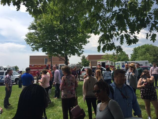 Staff members await further instructions following a full evacuation of NPHS due to a 2 alarm fire on Tuesday. Staff were dismissed after all students were able to safely leave the property.