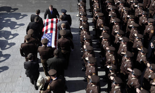 Members of the law enforcement community salute as St. Louis County police officer Blake Snyders casket is carried out of his funeral service Thursday, Oct. 13, 2016, in Chesterfield, Mo. Hundreds of police officers from around the country turned out to pay their respects for Snyder, who was fatally shot while on duty Oct. 6 after encountering a man accused of causing a disturbance in a normally quiet, middle-class suburban St. Louis neighborhood. (AP Photo/Jeff Roberson)