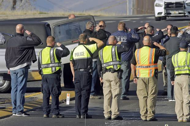 Police Officers salute as the body of Police Officer Cody Brotherson, 25, of West Valley City, Utah, is taken away from the scene where he was intentionally struck by a vehicle on November 6.  (AP Photo/Rick Bowmer)