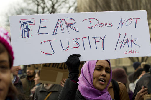 Demonstrators carrying signs chant as they protest outside of the White House during a demonstration to denounce President Donald Trump's executive order banning travel to the U.S. by citizens of Iraq, Syria, Iran, Sudan, Libya, Somalia or Yemen, Sunday, Jan. 29, 2017, in Washington.(AP Photo/Jose Luis Magana)