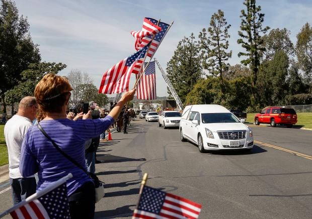 Citizens wave flags at a procession to honor slain Whittier police Officer Keith Wayne Boyer, arriving at the Rose Hills Memorial Park in Whittier, Calif., Friday, March 3, 2017. Boyer was killed Feb. 20 when he went to help a driver involved in a car crash, and the driver opened fire. (AP Photo/Nick Ut)