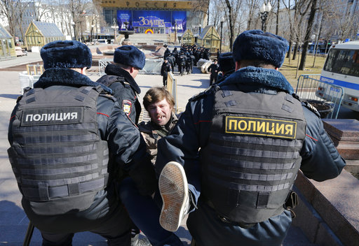 """Police detain a protester in downtown Moscow, Russia, Sunday, March 26, 2017. Russias leading opposition figure Alexei Navalny and his supporters aim to hold anti-corruption demonstrations throughout Russia. But authorities are denying permission and police have warned they wont be responsible for """"negative consequences"""" or unsanctioned gatherings. (AP Photo/Alexander Zemlianichenko)"""