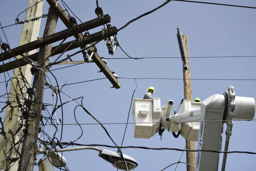 In this Thursday, Oct. 19, 2017 photo, a brigade from the Electric Power Authority repairs distribution lines damaged by Hurricane Maria in the Cantera community of San Juan, Puerto Rico. The storm struck after the Authority had filed for bankruptcy in July, put off maintenance and had finished dealing with outages from Hurricane Irma. (AP Photo/Carlos Giusti)