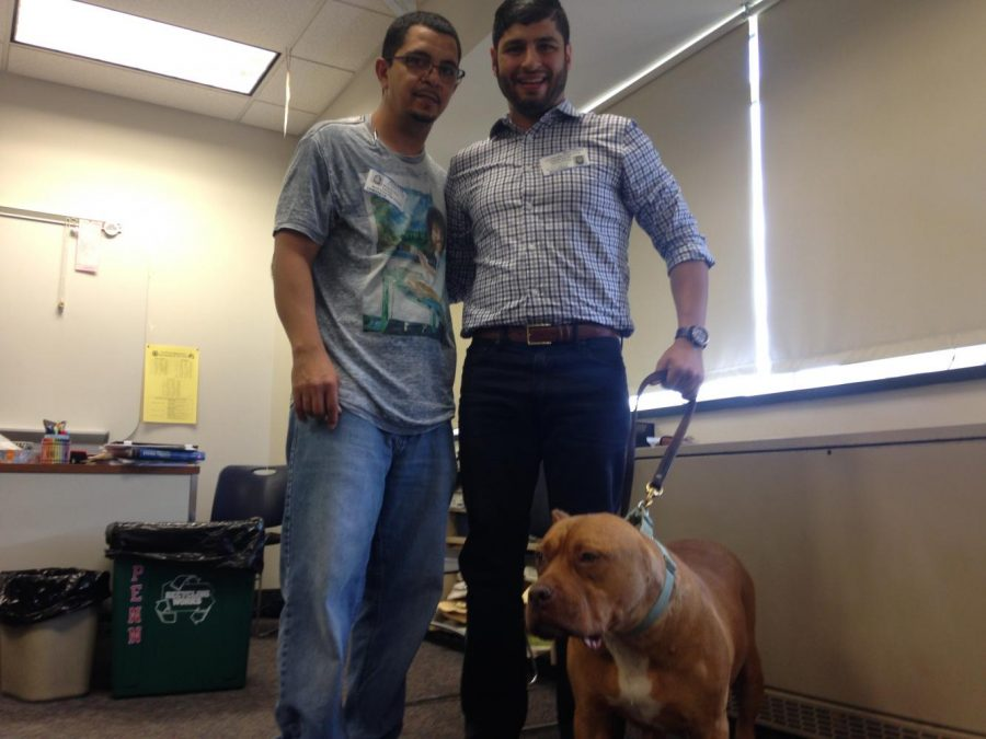 Norberto (Rob) Rosa (left) and Waleed Yousef (right) pose with rescue dog Rosie.