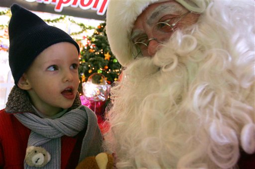 A man dressed as Santa Claus, right, listens to a young boy after the boy posed with Santa for a photograph in a Calais shopping center, northern France, Tuesday, Dec. 19, 2006. The shopping center is employing the performer during the Christmas period and is offering to let customers' children to have their photo taken with Santa. (AP photo/Michel Spingler)