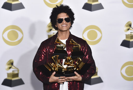 Bruno Mars poses in the press room with his awards for best R&B album, record of the year, album of the year, best engineered album, non-classical, for