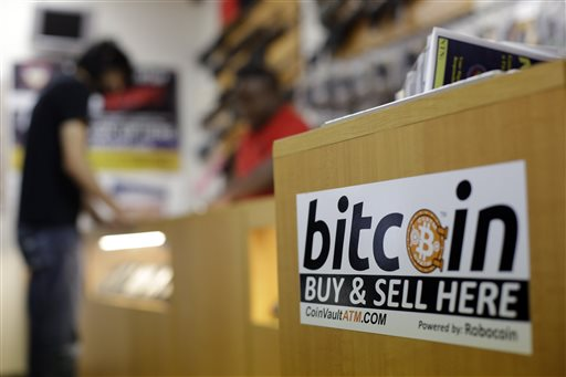 In this Wednesday, Aug. 20, 2014 photo, Jon Rumion, background left, talks with Michael Cargill at Central Texas Gun Works, in Austin, Texas. Rumion purchased two guns at the store using bitcoin. As states debate the merits of bitcoin, Texas is emerging as a vital testing ground for the digital currency. (AP Photo/Eric Gay)