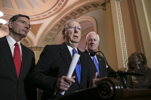 Senate Majority Leader Mitch McConnell, R-Ky., flanked by Sen. John Barrasso, R-Wyo., left, and Majority Whip John Cornyn, R-Texas, speaks to reporters about efforts to avoid a government shutdown this weekend, at the Capitol in Washington, Wednesday, Jan. 17, 2018. (AP Photo/J. Scott Applewhite)