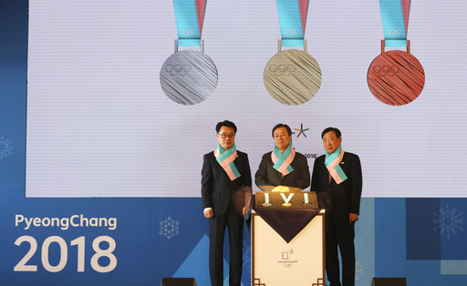 South Korean Culture, Sports and Tourism Minister Do Jong-hwan, center, Pyeongchang Organizing Committee for the 2018 Olympic and Paralympic Winter Games Lee Hee-beom, right, and Gangwon Province Vice Gov. Song Suk-doo stand with the silver, gold and bronze medals for the Pyeongchang 2018 Winter Olympics during an unveiling ceremony in Seoul, South Korea, Thursday, Sept. 21, 2017. South Koreas Pyeongchang is the host city of the winter games which will be held from February 2018. (AP Photo/Lee Jin-man)