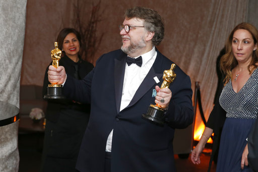Guillermo del Toro poses with his awards for best director and best picture for
