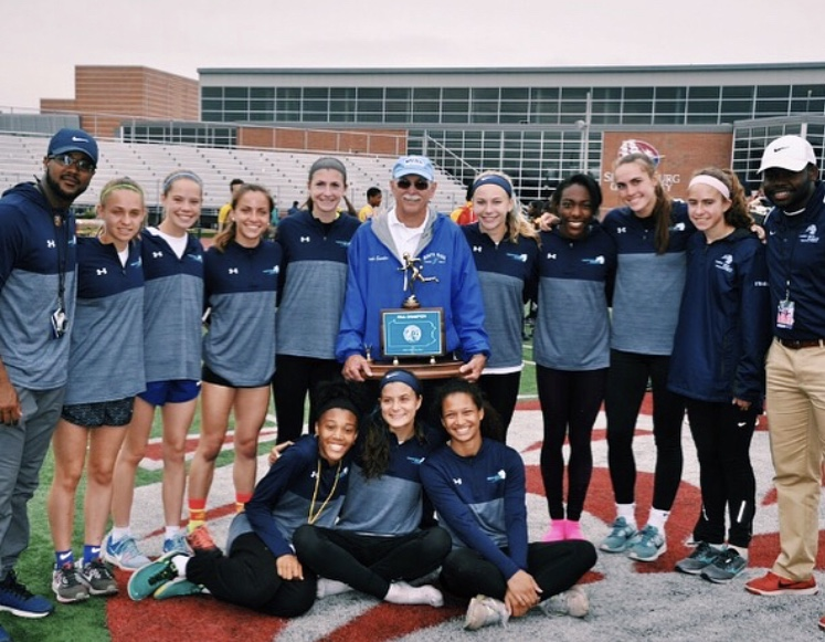 TRACK AND FIELD- The 2017 girls track and field team poses with their state championship trophy and former head coach, Richard Swanker.