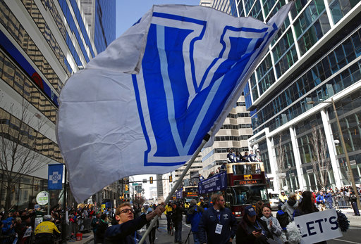 A student waves a Villanova flag in front of buses carrying members of the Villanova basketball team during a parade celebrating their NCAA college basketball championship, Thursday, April 5, 2018, in Philadelphia. Villanova defeated Michigan on Monday for the NCAA men's basketball title. (AP Photo/Patrick Semansky)