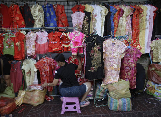 A vendor arranges traditional Chinese dresses or