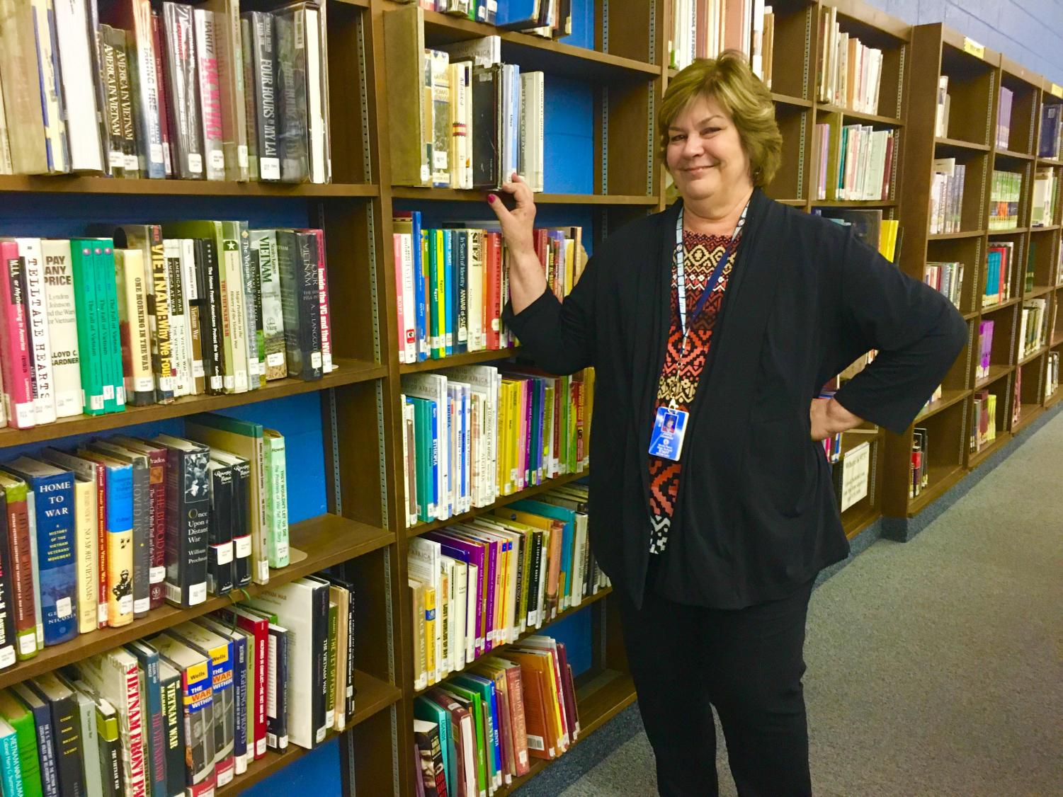 Library secretary Janice Johnson poses by the bookshelves. Johnson will retire this year.