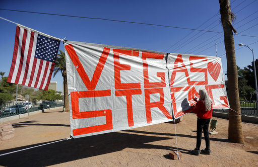 FILE - In this Oct. 5, 2017, file photo, Las Vegas resident Nancy Cooley signs a Vegas Strong banner honoring the victims of a mass shooting in Las Vegas. The official slogan of Las Vegas,
