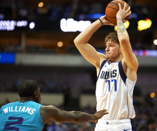 Dallas Mavericks' Luka Doncic (77) looks to pass the ball as Charlotte Hornets' Marvin Williams (2) defends during the first half of an NBA preseason basketball game Friday, Oct. 12, 2018, in Dallas. (AP Photo/Cooper Neill)