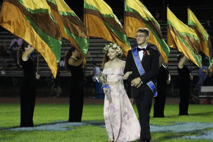Isaac Lambert walks down the football field with his sister Cassi during 2018 Homecoming.
