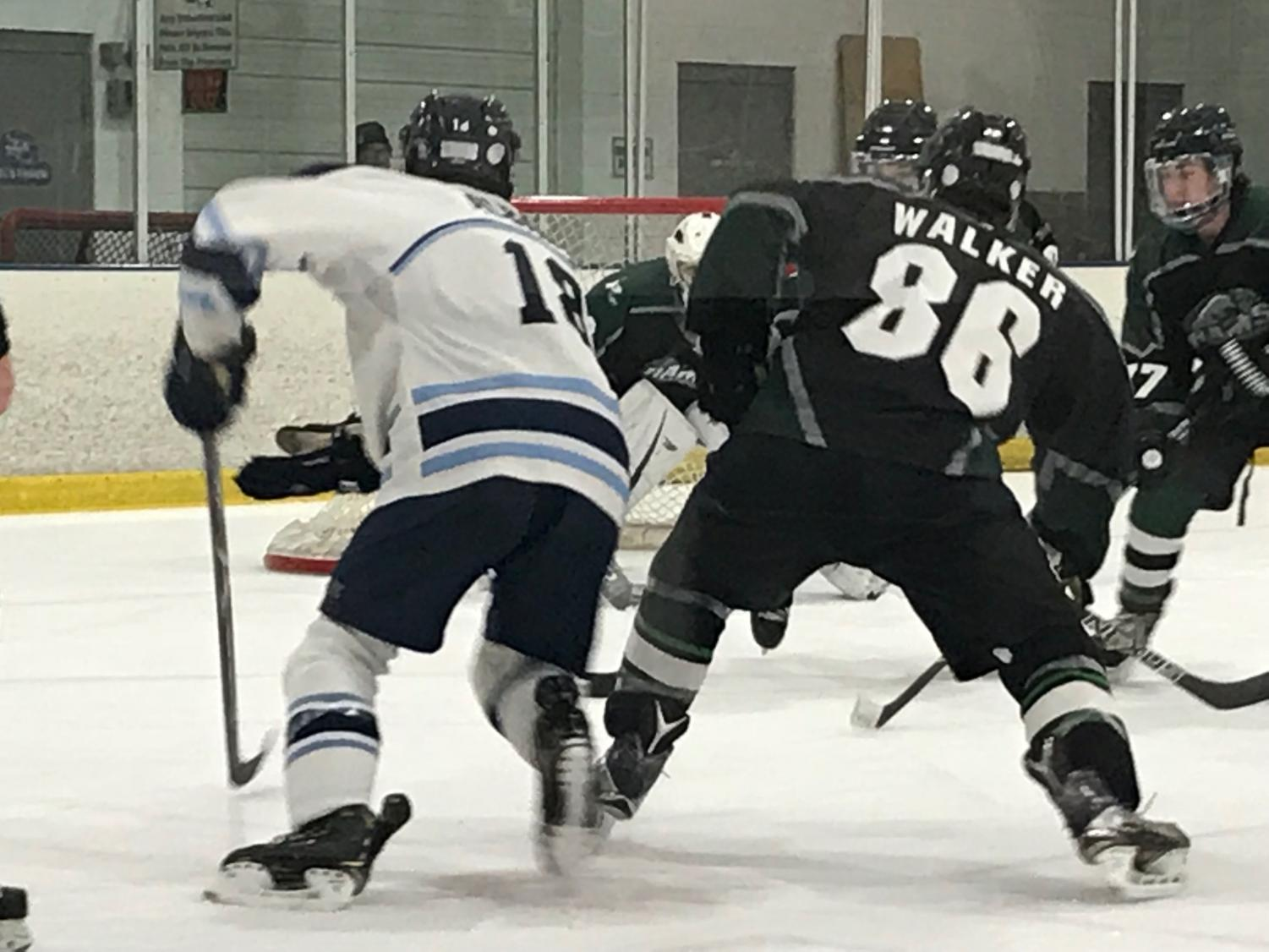 Jared Alabano battles for possession of the puck against a Rams defender