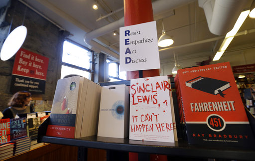 Books are displayed under a sign at the Harvard Book Store, Thursday, March 9, 2017, in Cambridge, Mass. Readers have been flocking to classic works of dystopian fiction in the first months of Donald Trump's presidency. Novels depicting dysfunctional societies have shot to the top of best-seller lists in recent months, including George Orwell's