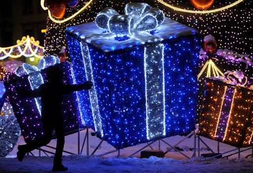 A child plays in front of a Christmas decoration resembling gifts on the Zamkowy Square in Warsaw, Poland,  Sunday, Dec 23, 2012, one day ahead of Christmas Eve. (AP Photo/Alik Keplicz)