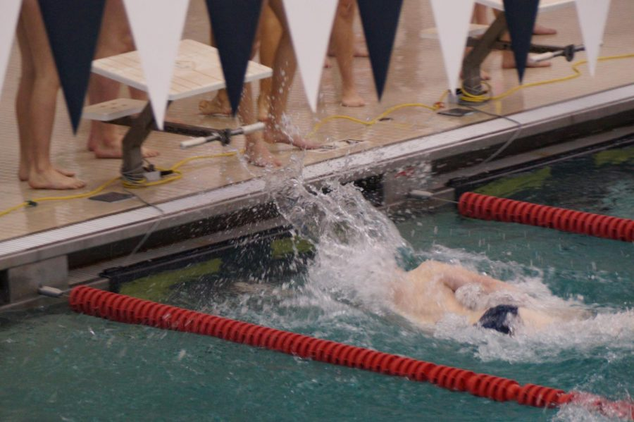 Junior Luke Schwar touches the wall as the Knights win the boys  200 medley relay.