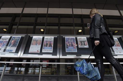 A woman views the front pages of newspapers on display outside the Newseum in Washington, Wednesday, Nov., 9, 2016, the day after the presidential election. (AP Photo/Susan Walsh)