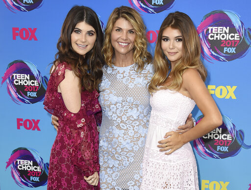 FILE - In this Aug. 13, 2017 file photo, actress Lori Loughlin, center, poses with her daughters Bella, left, and Olivia Jade at the Teen Choice Awards in Los Angeles. The FBI says actress Lori Loughlin has been taken into custody in connection with a scheme in which wealthy parents paid bribes to get their children into top colleges. FBI spokeswoman Laura Eimiller said Loughlin was in custody Wednesday morning in Los Angeles. She is scheduled to appear in court there in the afternoon. (Photo by Jordan Strauss/Invision/AP, File)