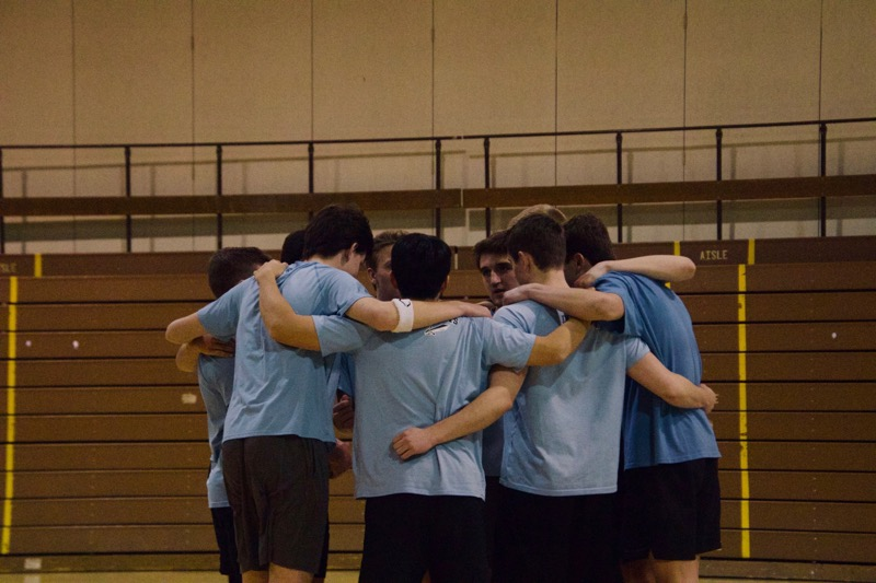 The soccer team volleyball squad gets into a huddle before the championship match with the Long Schwengs