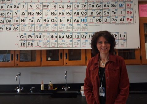 Mrs. Groat in front of her periodic table.