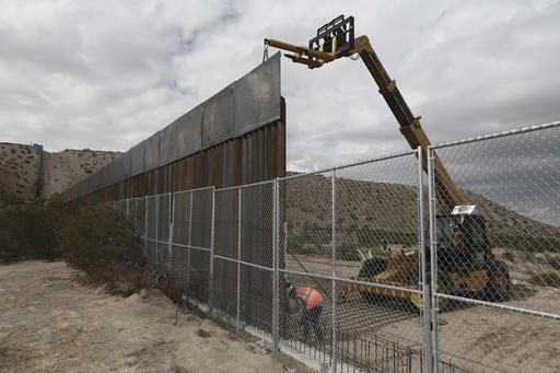 FILE - In this Nov. 10, 2016, file photo, workers continue work raising a taller fence in the Mexico-US border area separating the towns of Anapra, Mexico and Sunland Park, N.M. U.S. Customs and Border Protection said Friday, Feb. 24, 2017, that it plans to start awarding contracts by mid-April for President Donald Trump's proposed border wall with Mexico, signaling that he is aggressively pursuing plans to erect