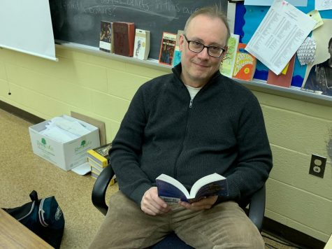 Mr. Mike Lipschutz reading a book at his desk.