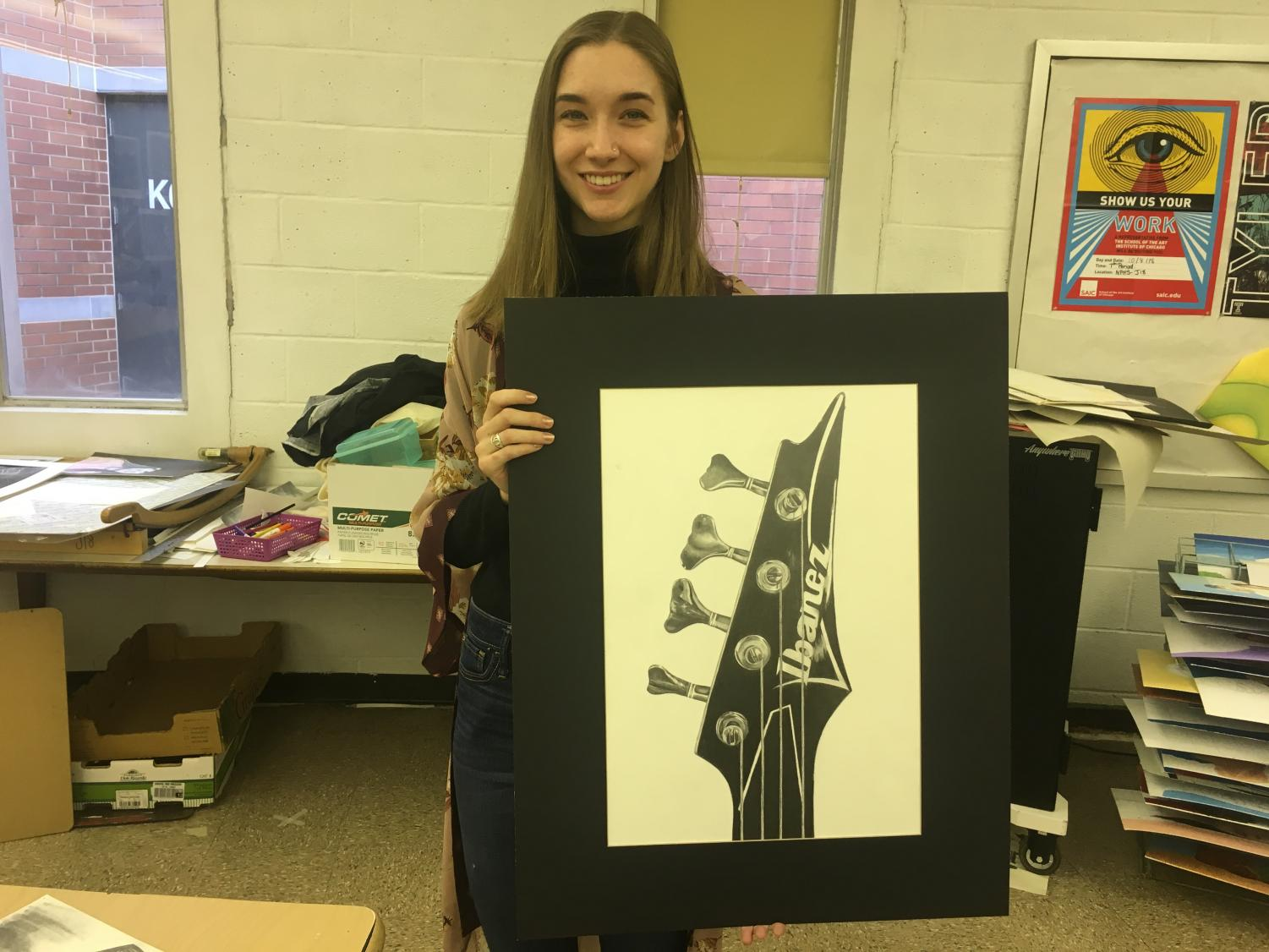 NPHS senior Anna Shinners poses for a picture with an art piece she has been working on this year.