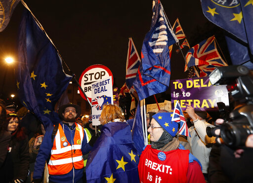 Pro and anti-Brexit supporters gather near the Parliament in London, Tuesday, Jan. 29, 2019. Britains Parliament is set to vote Tuesday on competing Brexit plans, with Prime Minister Theresa May desperately seeking a mandate from lawmakers to help secure concessions from the European Union. (AP Photo/Alastair Grant)