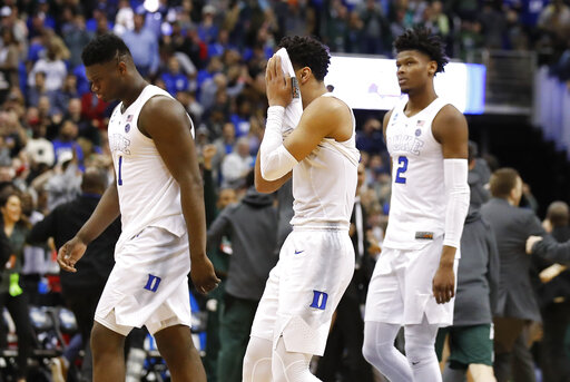 Duke guard Tre Jones, center, covers his face as he walks off the court with teammates Zion Williamson (1) and Cam Reddish (2) after losing to Michigan State in the NCAA men's East Regional final college basketball game in Washington, Sunday, March 31, 2019. (AP Photo/Alex Brandon)