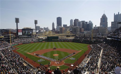The Pittsburgh skyline is seen beyond the outfield walls at PNC Park as the teams line up on the baselines during the playing of the national anthem before the Pirates home opener baseball game against the Colorado Rockies, Thursday, April 7, 2011 in Pittsburgh. (AP Photo/Keith Srakocic)