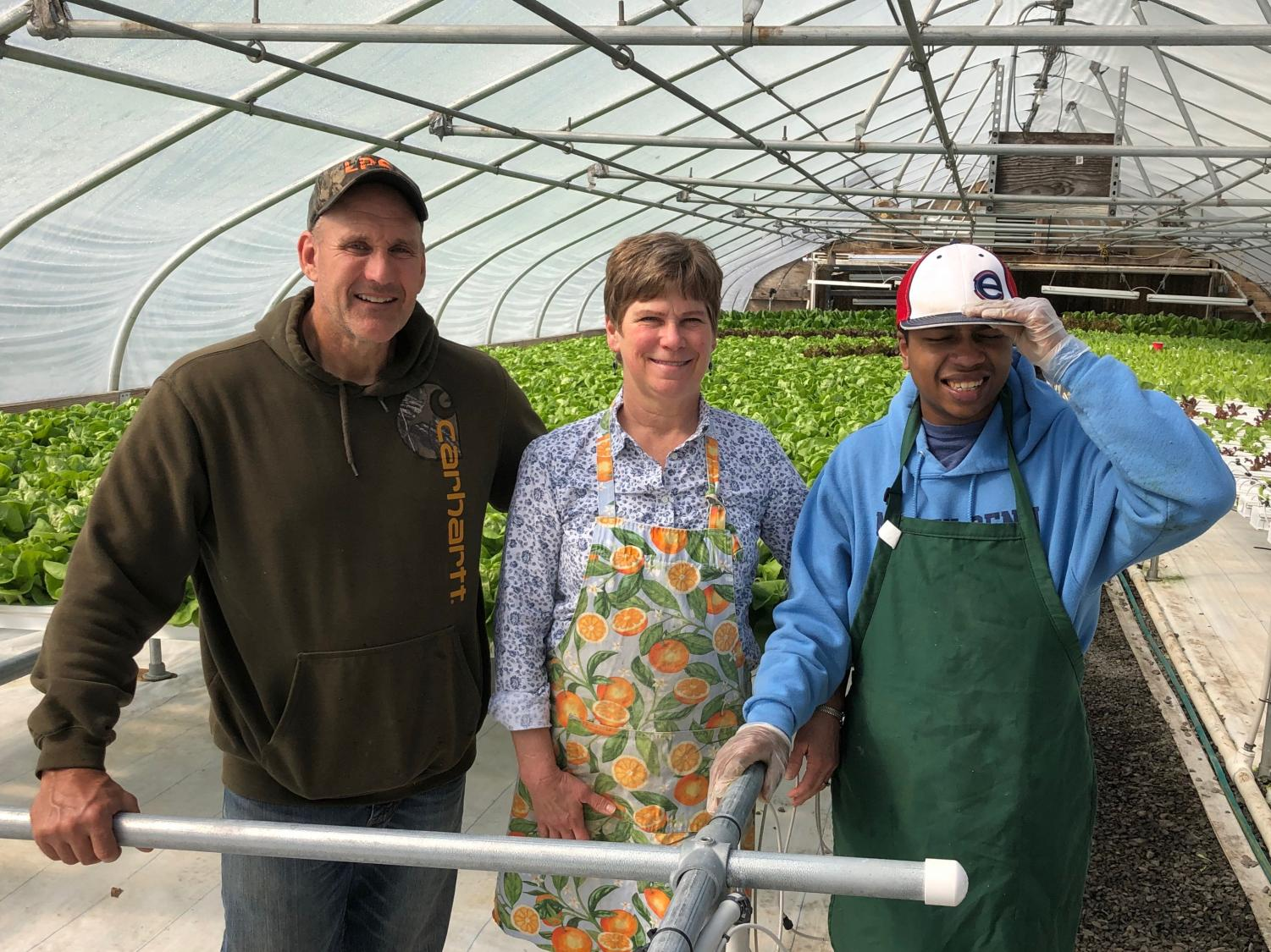Landes with a student at GreenWorks Farm, a site she takes students to as a job coach.