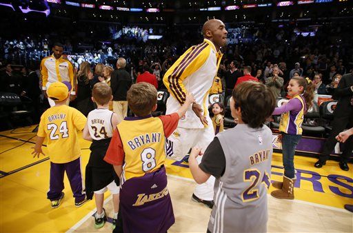 Los Angeles Lakers' Kobe Bryant is greeted by young fans wearing his jersey as he comes onto the floor before the NBA basketball game against the Toronto Raptors  in Los Angeles, Sunday, Dec. 8, 2013. Bryant is expected to make his long-awaited return from a torn left Achilles tendon injury from April 12th. (AP Photo/Danny Moloshok)