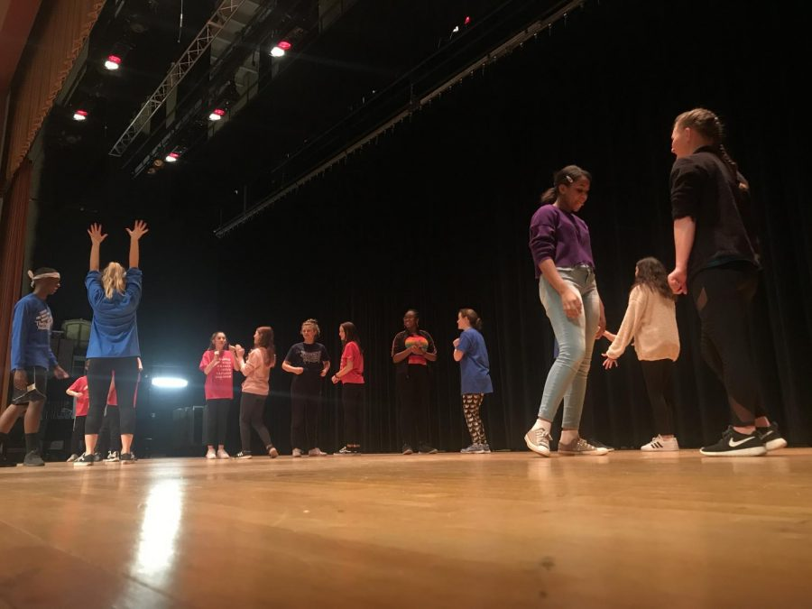 Middle schoolers practice a partner routine from