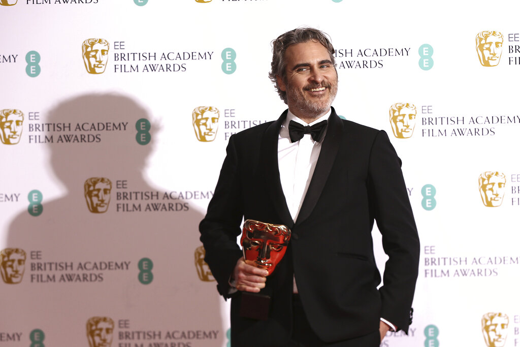 Actor Joaquin Phoenix poses with his award for Best Actor for the film Joker, backstage at the Bafta Film Awards, in central London, Sunday, Feb. 2, 2020. (Photo by Joel C Ryan/Invision/AP)