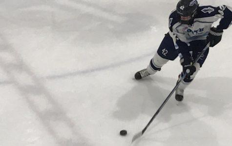Jeromy Porubski carries puck for North Penn across center ice.