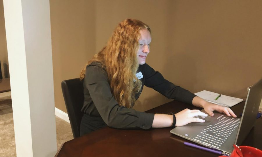 Junior Ashley Kitch in front of her computer screen participating in online school.