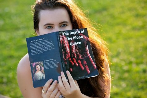 "Mya Richter posing with her first published book ""The Death of the Blood Queen."""