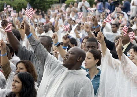 Bianera Petithomme, center, of Haiti, waves a flag and cheers after becoming a U.S. citizen during a naturalization ceremony at Walt Disney World in Lake Buena Vista, Fla., Wednesday, July 4, 2007.