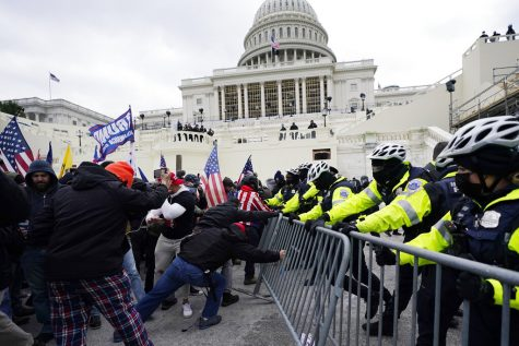 FILE - In this Jan. 6, 2021, file photo, Trump supporters try to break through a police barrier at the Capitol in Washington. For America