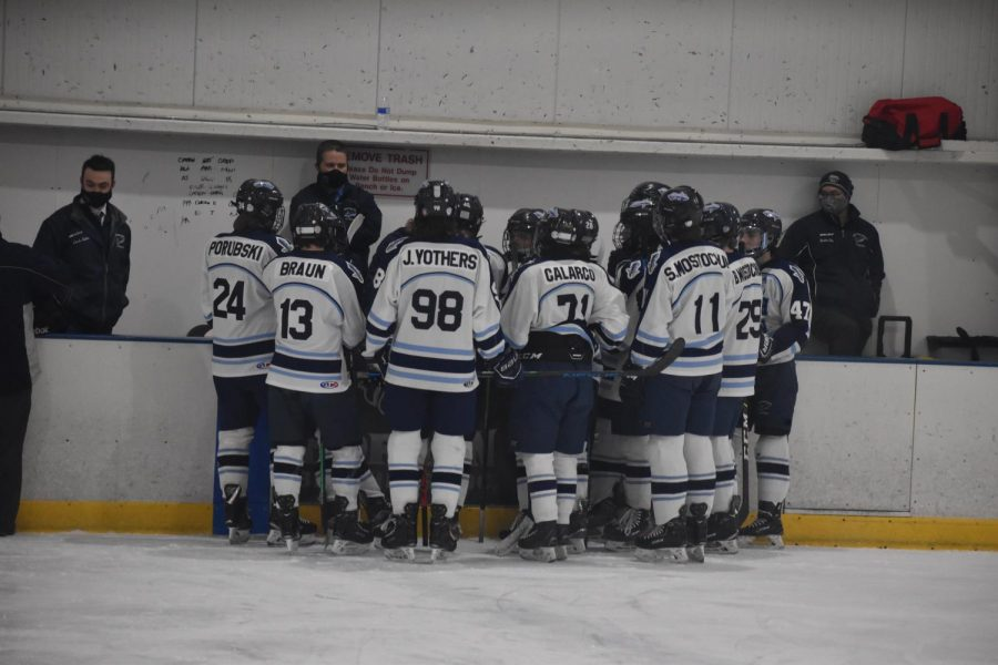 The North Penn Knights gather around head coach Kevin Vaitis for last minute pregame instructions.